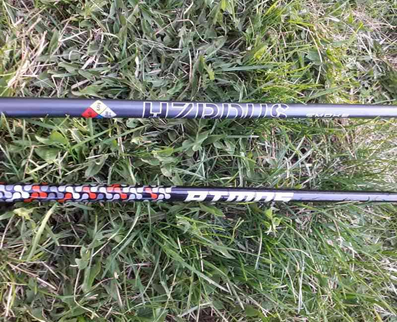 Graphite golf shafts laying on grass