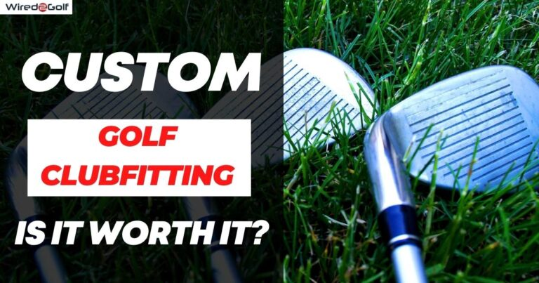 golf irons laying on grass.