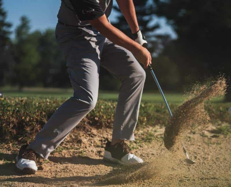 golfer hitting a shot from the sand