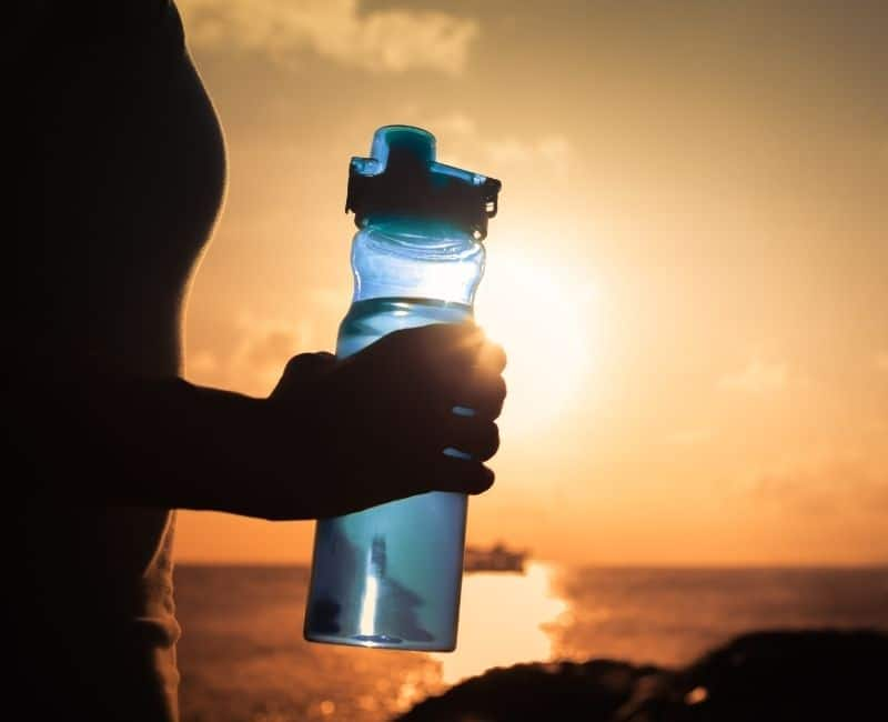 person holding water bottle in orange sunset